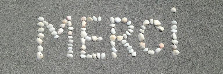 Merci écrit dans le sable